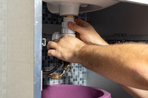 Plombier Blois - Un plombier répare le siphon d'un ballon d'eau chaude.