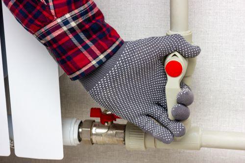 Plombier Blois - Un plombier ferme un circuit d'eau de radiateur.