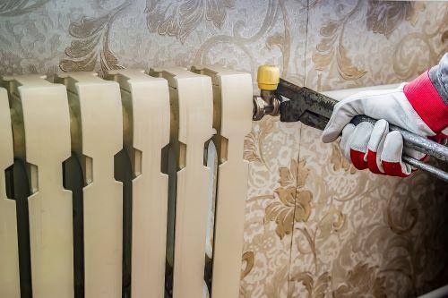 Plombier Boulogne-sur-Mer - Un artisan répare un radiateur.