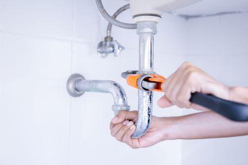 Plombier Bourg-en-Bresse - Un artisan répare un évier qui fuit à l'aide d'une clé à molette.