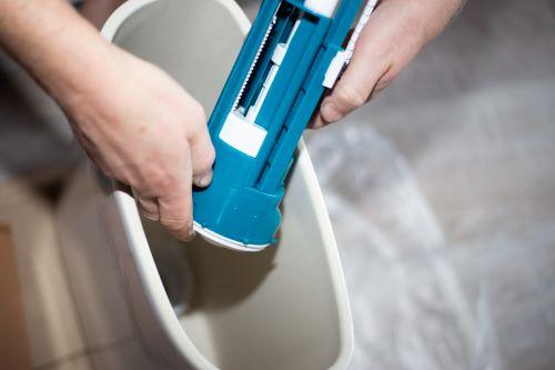 Plombier Bron - Un plombier installe une pompe à eau dans un réservoir attenant de toilette en céramique.
