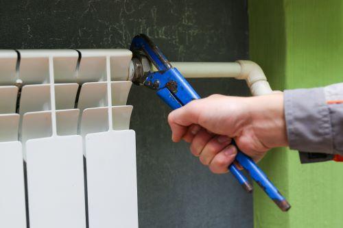 Plombier Bron - Un plombier serre le tuyaux d'un chauffage.
