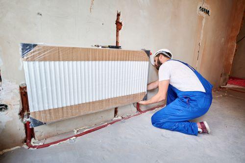 Plombier Brunoy - Un plombier chauffagiste installe un radiateur.