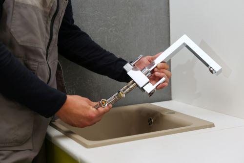 Plombier Carcassonne - Un plombier installe un robinet de cuisine.