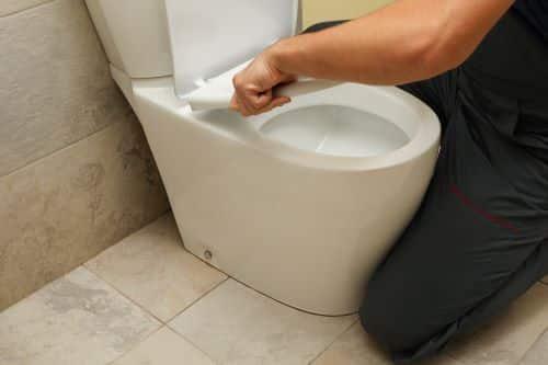 Plombier Châteauroux - Un artisan installe des toilettes.