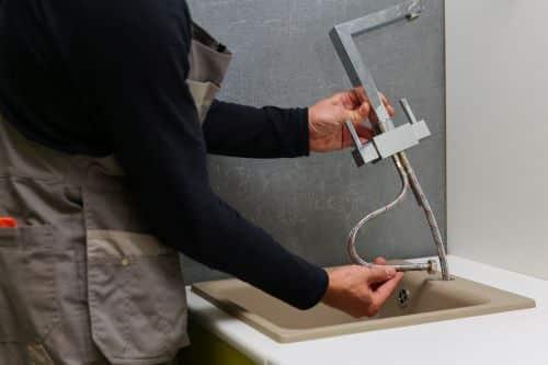 Plombier Châteauroux - Un plombier procède au remplacement d'un robinet de cuisine.