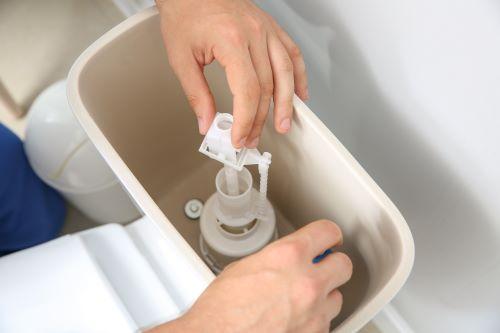 Plombier Colomiers - Un plombier répare le bac d'un toilette.
