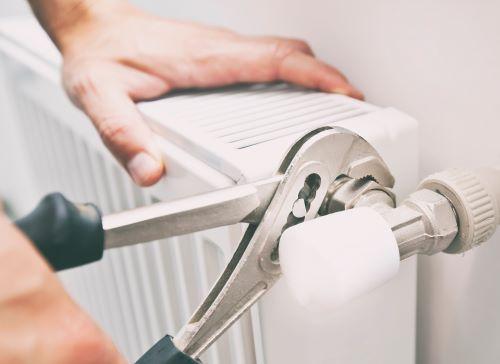 Plombier Draguignan - Un plombier répare l'arrivé d'eau d'un radiateur.