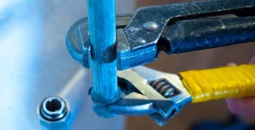 plombier draguignan - un artisan installe un circuit de plomberie avec deux clés de serrage