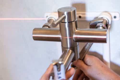 Plombier Franconville - Un artisan installe un mitigeur.