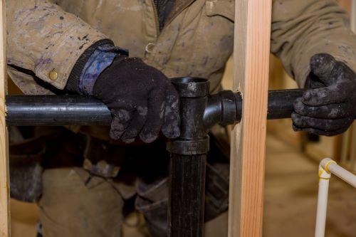 Plombier Le Cannet - Un plombier installe des tuyaux en PVC.