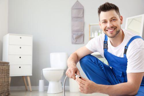 Plombier Montfermeil - Un plombier travaille sur des toilettes.