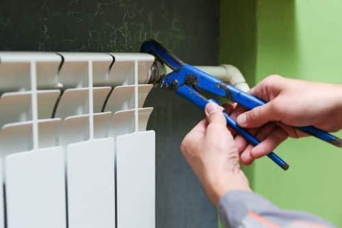 Plombier Neuilly-sur-Marne - Un artisan remplace les pièces d'un radiateur.