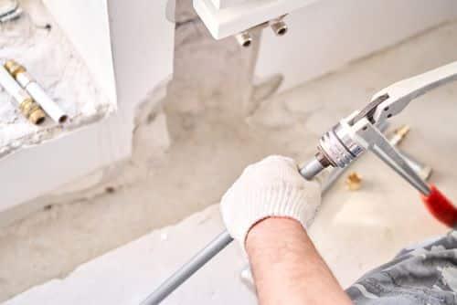 Plombier Pontoise - Un plombier effectue des travaux sur un système de chauffage.