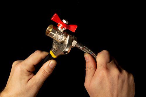 Plombier Rezé - Le plombier connecte un tuyaux à une vanne.
