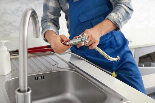 Plombier Romainville - Un plombier installe un robinet de cuisine.