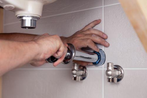 Plombier Romainville - Un plombier répare le siphon d'un lavabo d'une salle de bains.
