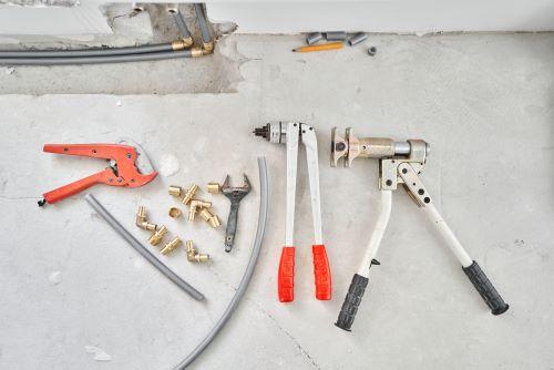 Plombier Saint-Brieuc - Divers outils de plomberie posés au sol.