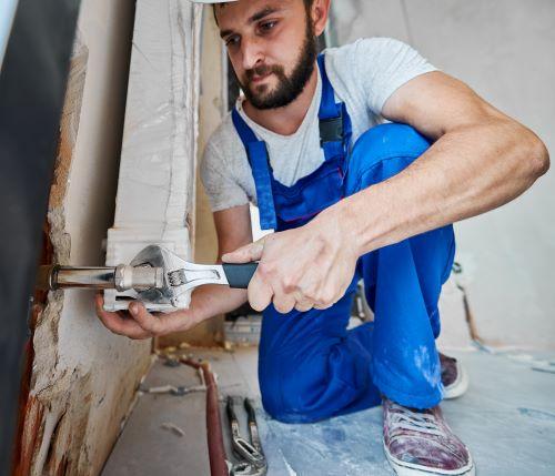 Plombier Saint-Ouen-l'Aumône - Un plombier installe un radiateur.