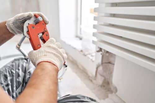 Plombier Salon-de-Provence - Le artisan coupe un tuyau lors de l'installation d'un radiateur.