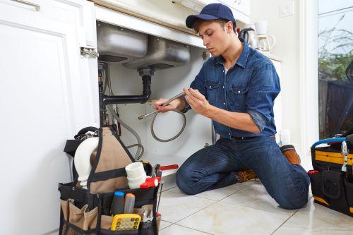 Plombier Sannois - Un plombier répare les canalisations d'un évier.