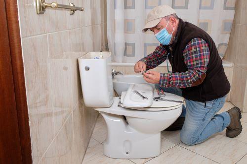 Plombier Talence - Un artisan installe des toilettes.