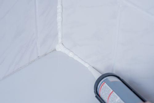 Plombier Talence - Application d'un joint sur les carreaux d'une salle de bains.