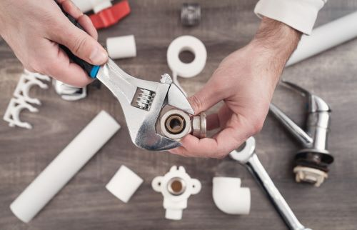 Plombier Tarbes - Un plombier répare un robinet d'eau avec ses outils.