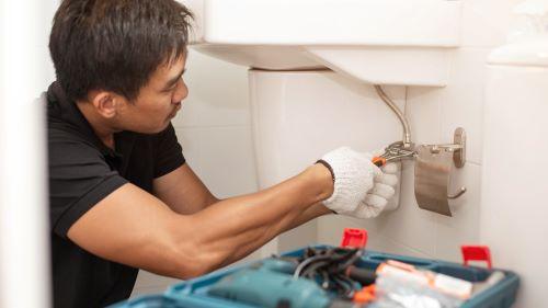 Plombier Taverny - Un artisan intervient sur des toilettes en panne.