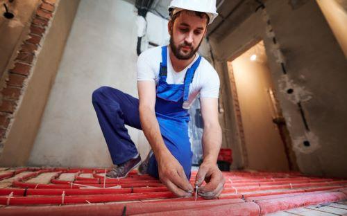 Plombier Taverny - Un artisan met en place un chauffage au sol dans une nouvelle maison.