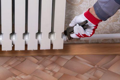 Plombier Thionville - Un plombier raccorde un radiateur en fonte au système de chauffage d'une maison.