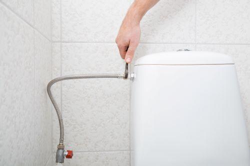 Plombier Vaulx-en-Velin - Un artisan le tuyau d'une arrivée d'eau sur des toilettes.