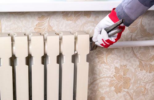 Plombier Wattrelos - Un artisan vérifie vérifie l'étanchéité d'un radiateur.