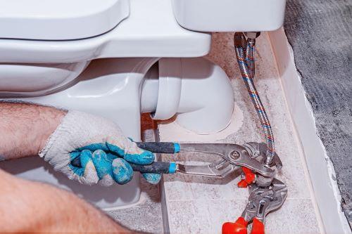 plombier Brétigny-sur-Orge - un plombier raccorde un flexible à des toilettes