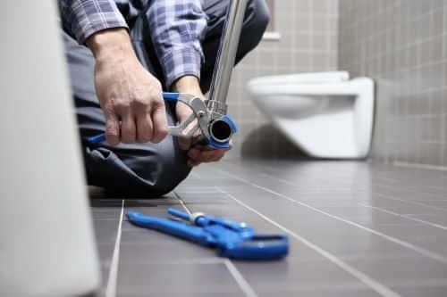 plombier Goussainville - un artisan installe un robinet dans une salle de bains