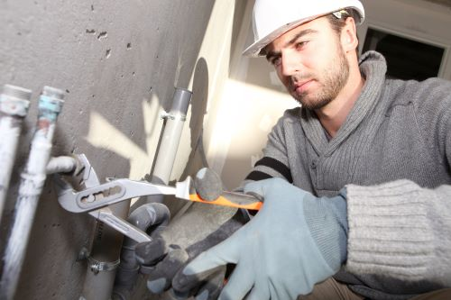 plombier Grigny - un artisan installe un circuit de plomberie dans une maison en construction