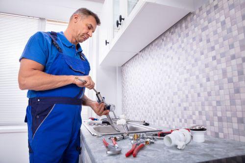 plombier Guyancourt - un artisan intervient dans une cuisine