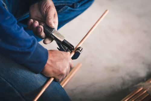 plombier L'Haÿ-les-Roses - un artisan avec un coupe-tube prépare un circuit de chauffage