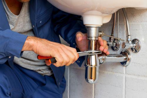 plombier L'Haÿ-les-Roses - un artisan installe un siphon sur un robinet neuf