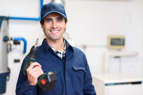 plombier Le Chesnay-Rocquencourt - un artisan souriant tient une perceuse