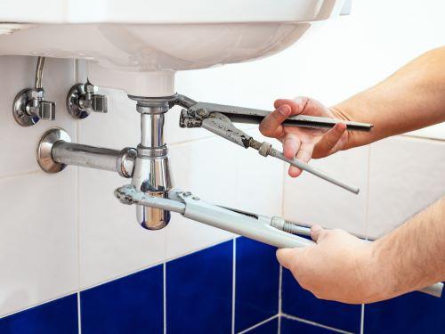plombier Le Plessis-Robinson - un homme desserre un siphon de lavabo