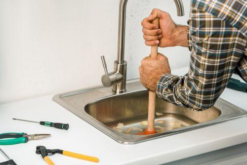 plombier Malakoff - un artisan débouche un évier avec une ventouse