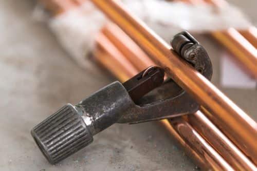 plombier Palaiseau - un coupe-tube et des tuyaux en cuivre