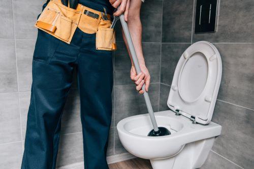 plombier Thiais - un artisan débouche des toilettes avec une ventouse
