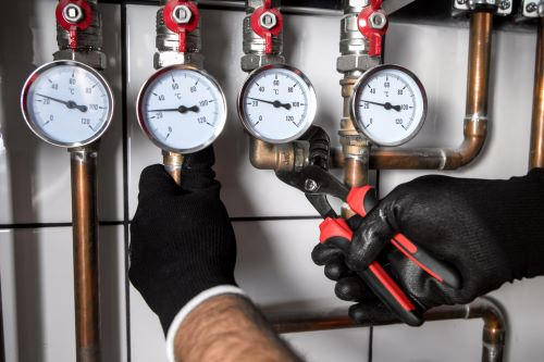plombier Trappes - un artisan règle la nourrice d'un réseau de chauffage