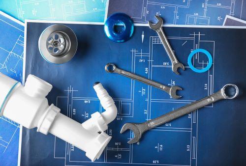 plombier Vigneux-sur-Seine - un siphon et des outils de plomberie sur un plan de construction