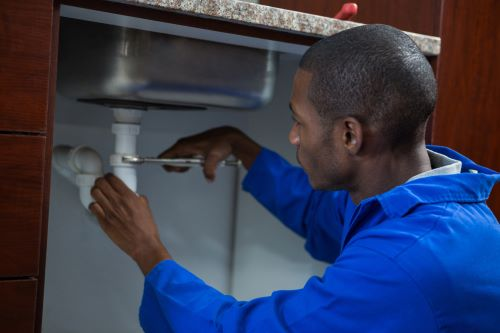 plombier Villiers-le-Bel - un artisan répare le siphon d'un évier