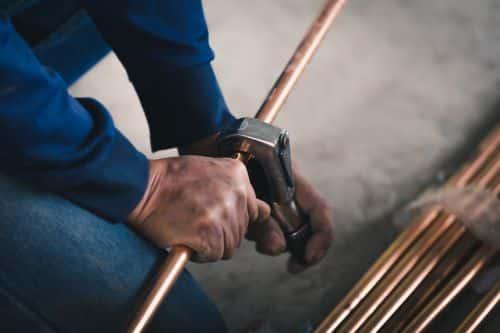 plombier Viry-Châtillon - un artisan découpe des tuyaux de cuivre pour installe un circuit de chauffage