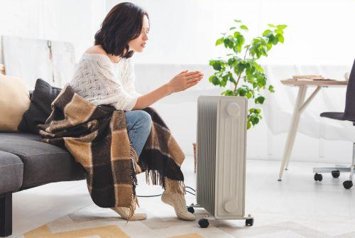 Chauffagiste Toulon - Une femme se réchauffe avec un chauffage mobile
