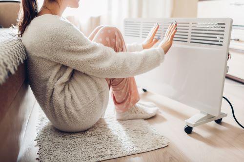 Chauffagiste Annecy - Une femme se réchauffe auprès d'un radiateur.